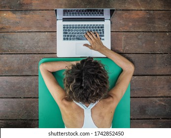 bird view of a sportive woman with laptop typing and getting ready for online fitness pilates workout lying on her stomach on on a green yoga mat on wooden floor
