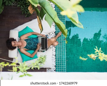bird view of a successful remote online working digital nomad women with curly hair with laptop lying at a sunny turquoise water pool surrounded by cushions and plants in the foreground