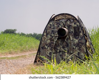 Bird watcher hiding in the blind tent with his telephoto camera waiting for the bird