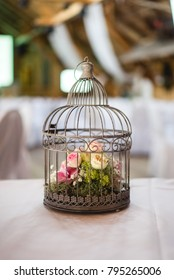Birdcage with pink and yellow roses; decoration for a wedding party