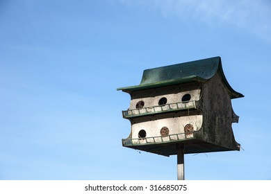 Birdhouse alone against a blue sky. Nests visible