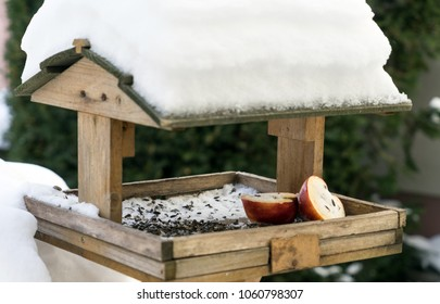 Birdhouse covered with snow and birdseed