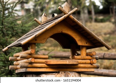Birdhouse on a tree hanging from a branch. Wooden birdhouse made of small logs. Birdhouse on blurred city background. Handcrafted log cabin birdhouse. Save animals
