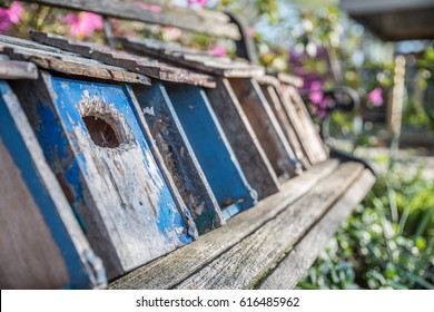 Birdhouses laying on a rustic, wooden bench
