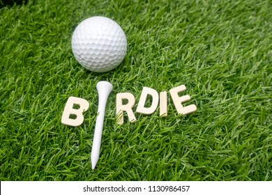 Birdie with golf ball is on green grass