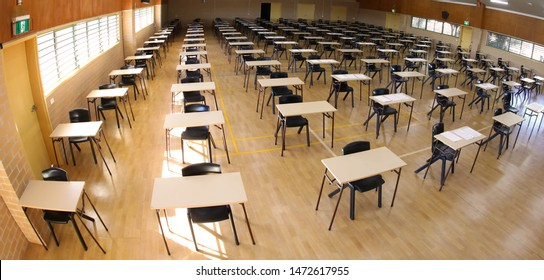 birds eye from above inside view of am examination exam hall room set up empty ready for a test to be taken by school students. Plain rectangle desks and black chairs arranged for assessment.