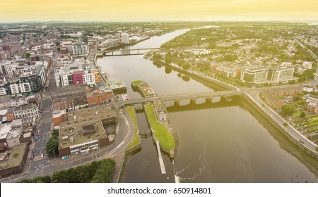 Birds Eye Aerial view cityscape of limerick city skyline. Ireland's 3rd largest city. Large Irish urban Limerick city skyline with skyscraper over the Shannon River. Sunshine ray sky effect added.