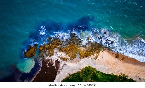 Bird's eye top aerial view of waves hitting a group of rocks on a beautiful tropical beach in Tabatinga, Brazil located near Joao Pessoa. The rocks create a beautiful pattern.
