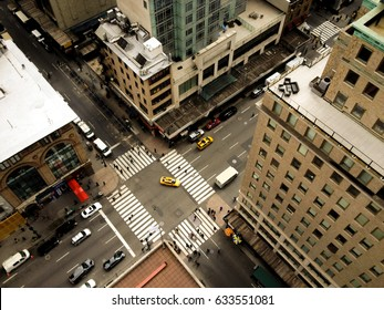 Birds eye view of 5th Avenue, a yellow taxi makes a left hand turn. Looking down on Midtown Manhattan's Fifth Avenue, zebra crossing and people going to work.