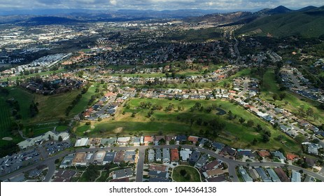 Birds eye view aerial drone perspective of San Marcos California, golf course, university, city, and distant hills, under cloud shadow in north county San Diego