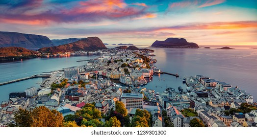 From the bird's eye view of Alesund port town on the west coast of Norway, at the entrance to the Geirangerfjord. Colorful summer sunset at the Nord port. Traveling concept background.