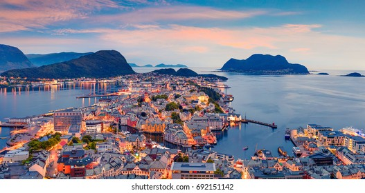 From the bird's eye view of Alesund port town on the west coast of Norway, at the entrance to the Geirangerfjord. Colorful sunset in the North. Traveling concept background.