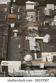 A bird's eye view of a buildings roof with antennas, AC vents, and ventilation.