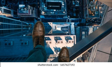 Bird's eye view from the clear glass deck on top of a high rise building. In the photo are the legs of a man in elegant shoes.