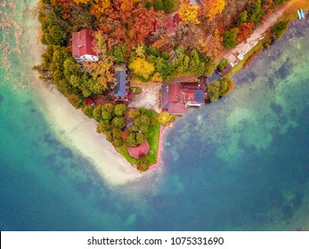Birds eye view of colorful trees and houses on a lake