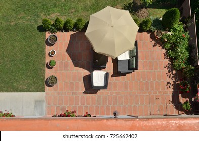 Bird's eye view of garden furniture under parasol surrounded by garden plants