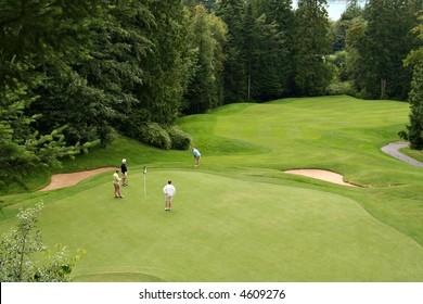 Bird's eye view of golfers on a beautiful putting green.