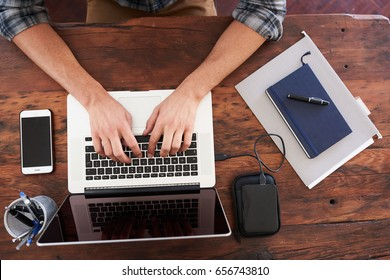 Birds eye view of hands typing on a modern notebook, placed on a durable dark wood desk along with some notes, portable storage, a pen holder and a mobile phone.
