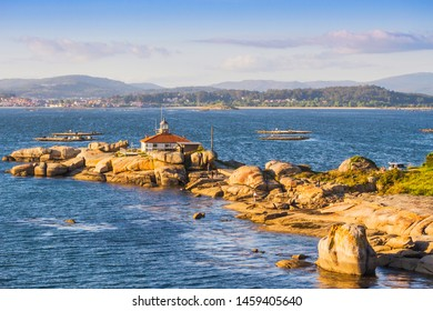 Bird's eye view of the lighthouse over the coastal rocks in Punta Cabalo cape, Arousa Island, Galicia