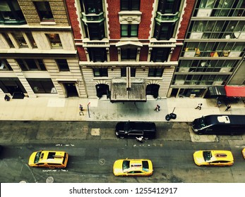 Bird's eye view of midtown Manhattan from a tall skyscraper. Looking down on New York yellow taxis and busy street of New York City. Looking down on taxis driving down the street, crossed processed.
