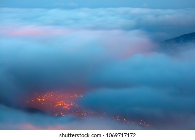Bird's eye view on Faraya mountain, Lebanon, amazing view from above through clouds on mountainous city, glowing lights from the homes windows at night