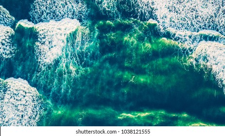 Bird's eye view on the open waters of planet earth, stormy seas, blue turquoise water of an ocean with waves and foam, abstract natural background, drone photography