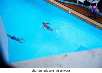 a bird's eye view photo of two swimmers swimming in the blue water pool with a trainer walking at the pool edge in the morning atmosphere