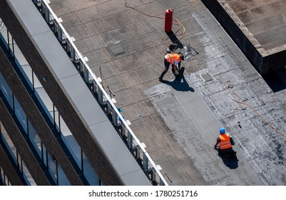 Birds eye view of a roof construction site. Professional bitumen waterproofing on a flat building.