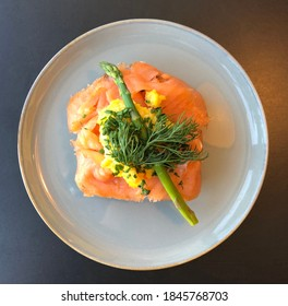 Birds eye view of scandinavian speciality smorrebrod with smoked salmon, asparagus and dill on top - served on a white plate with black background