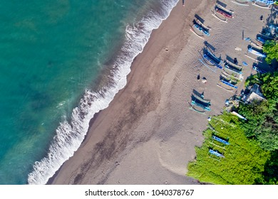 Birds eye view of Seseh Beach with traditional wooden boats called jukung, nearby Canggu and Tanah Lot Temple, Bali, Indonesia.