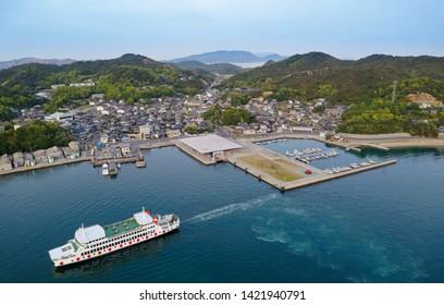 A bird's eye view of a ship navigating in Miyanoura Port and fishing boats moored to the dock, with village houses sprawling between the harbor & the hills in Naoshima island, Kagawa, Shikoku, Japan