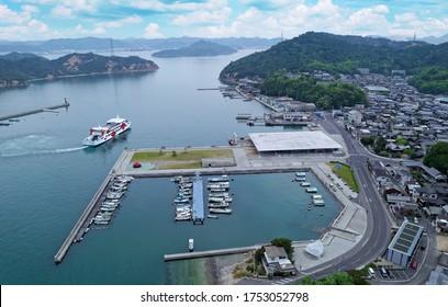 A bird's eye view of a ship navigating in Miyanoura Port and fishing boats moored to the docks, with village houses sprawling between the harbor & the hills in Naoshima island, Kagawa, Shikoku, Japan