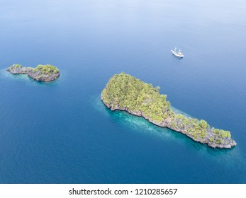 A bird's eye view shows dramatic limestone islands rising from the peaceful seascape in Raja Ampat, Indonesia. This remote, tropical region is known for its spectacular marine biodiversity.