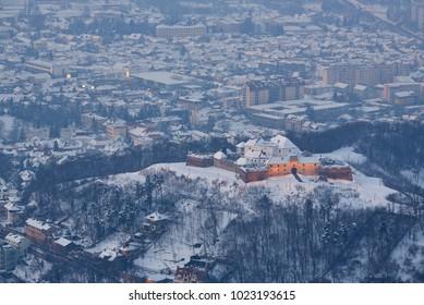 Bird's eye view of the snowy medieval citadel of Brasov, Transylvania, Romania. Aerial winter cityscape.