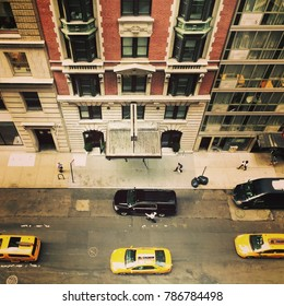 Birds eye view of a street in New York City with three yellow taxis and people walking down the sidewalk. Looking down on the streets of New York, midtown Manhattan.