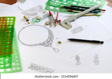 From a bird's eye view, there are sketches, jewelry, and many accessories used for drawing on the table.