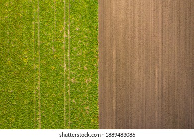 Bird's eye view of tractor tracks in a green field and in a brown field in the south of Germany