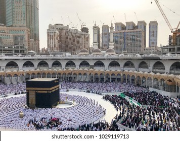 Bird's eye view of unidentified Muslim pilgrims in standing position facing the Kaabah during day time.