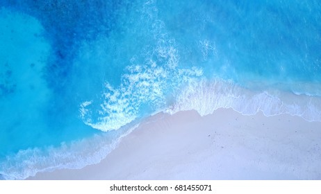 Bird's eye view of waves on white sand beach in Maldives