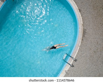 Birds eye view, young girl in black swimsuit, jumps into a swimming pool.