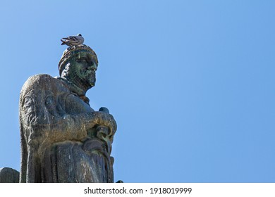 Birds living in urban areas cause significant damage to historical monuments and statues. A medieval knight statue in Tarifa is covered with unsightly bird droppings. A pigeon is perching on the head.