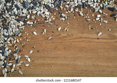 Birdseed spilled on brown wood table top.  Variety of different seeds for birds as background texture concept with space for copy for website.