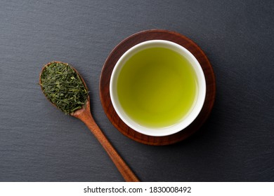 A bird's-eye view of green tea placed on a black background with space. Image of Japanese green tea.