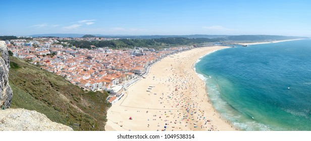 Bird's-eye view on Nazare beach riviera on the coast of Atlantic ocean with Nazare town. Portugal