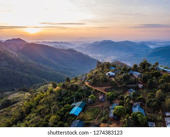 A bird's-eye view of a Thai town between the mountains. On the far horizon the sun is set to calm down.