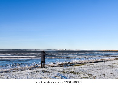 Birdwatcher by an icy coast in winter season at the swedish island Oland