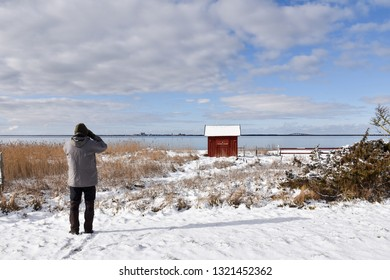Birdwatcher looking for birds in winter season by the coast of swedish island Oland
