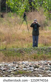 Birdwatcher photographing an Ibisbill in a river in China.