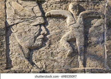 BIRGI, TURKEY - JANUARY 31, 2017: Sculpture over a rock wall representing Ataturk and a person performing local folk dance of Zeybek, in Birgi, Turkey.