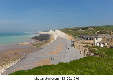 Birling gap beach and Seven Sisters white chalk cliffs East Sussex England UK with tide out